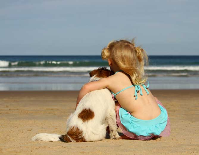 Little girl and her dog on the beach