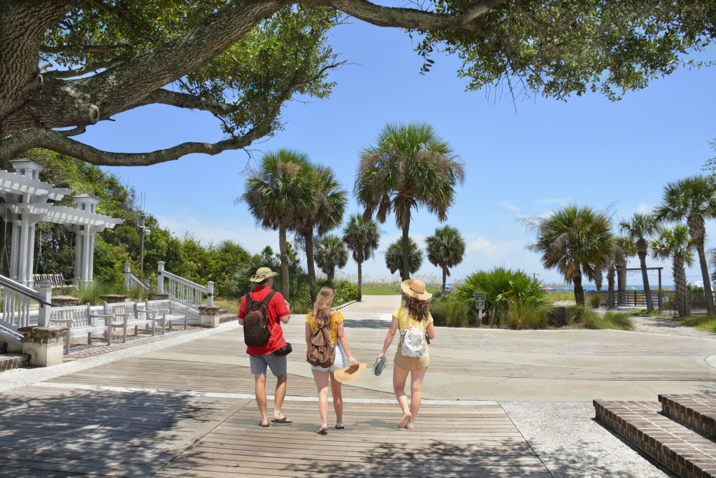 People enjoying summer vacation by the ocean. Palm trees on the pathway leading to ocean. Coligny Beach Park, Hilton Head Island, South Carolina, USA