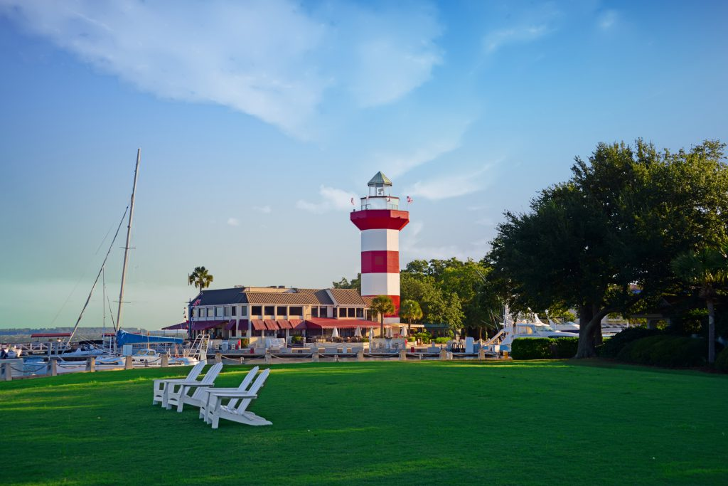 lighthouse red and white stripes, lawn green grass, two chairs on lawn, building in background, blue sky with white clouds