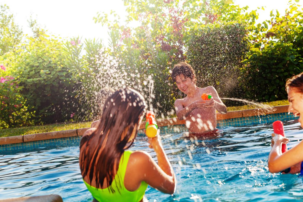 Group of three teens play with water-gun squirt pistol on swimming pool outside on sunny day